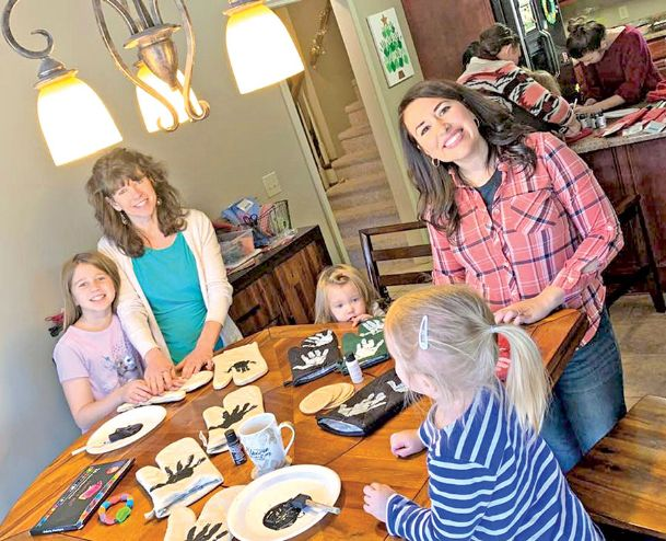Moms Casey Erickson, left, and Ivy Harris of Columbus help two of Erickson's children and a playmate with an activity during a MOPS play date. Susie Erickson, 10, is standing far left. Two-year-old Josie Erickson, center, peeks over the table. Erickson and Harris belong to a MOPS — Mothers of Preschoolers — group that meets twice monthly at Main Street Presbyterian Church. MOPS groups also plan outings, game nights, ladies night out and other activities.