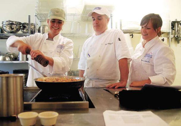 Carol Dowdy seasons a dish of ratatouille as Chef Erich Ogle, director of Mississippi University for Women's Culinary Arts Institute, and Tiana Schultz look on. Dowdy is culinary arts instructor at McKellar Technology Center in Columbus. She and Schultz were among 30 high school culinary arts educators at the ProStart Institute held at MUW July 25-29.