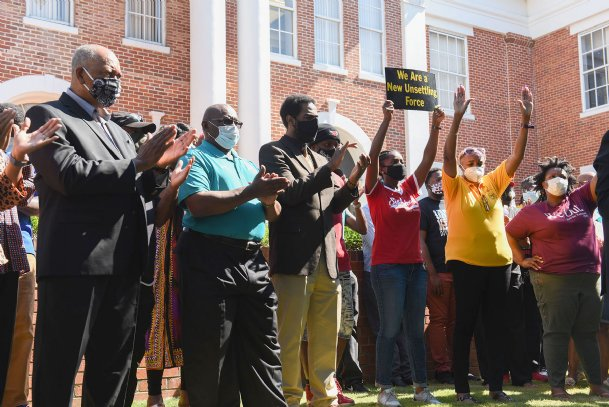 City officials and other community leaders cheer as District 41 Rep. Kabir Karriem speaks during a protest demanding Lowndes County Board of Supervisors President Harry Sanders' resignation on Wednesday on the Lowndes County Courthouse lawn.
