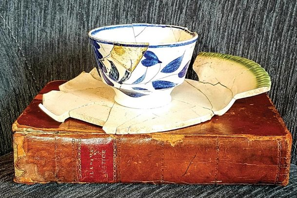 Artifacts of Columbus' beginnings. A broken plate and tea cup from the early 1820s found at one of Columbus' oldest house sites are resting on one of Alabama's first law books