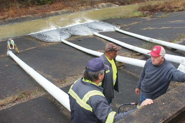 Bell Schoolhouse volunteer firefighter Walker Harris, far left, county road foreman Mark Vaughn, road operator Doug Clark and retired maintenance worker Robert Howell work on the pipes carrying water from the Oktibbeha County Lake Dam to the emergency spillway Tuesday afternoon. The county issued a warning to area residents the dam was in