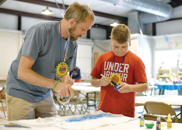 Camp Rising Sun counselor Jason Kirkland helps camper Bo Carter tape his T-shirt to a table so it won't move while he paints it Tuesday. Kirkland has been coming to camp since it began in 1987.