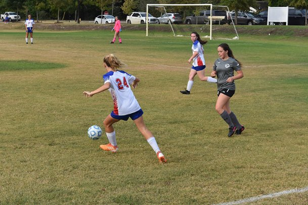 Heritage Academy's Chloe Boyd (24) moves the ball away from a Laurel attacker as teammate Hanna Hardy, back, maintains a defensive position.
