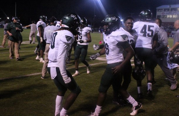 West Point defensive backs Joqwan Young (10) and Frederick McMillian (26) celebrate after McMillian's interception in the fourth quarter of Friday's game at Grenada. The Green Wave won 28-14 and will face Ridgeland on the road next Friday in the MHSAA Class 5A semifinal round.