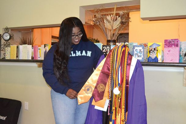Marian Turner, 17, shows off her graduation honor cords while wearing her Spelman College sweatshirt at her home Tuesday morning. Turner graduated valedictorian of Columbus High School with a 4.581 GPA and simultaneously graduated from East Mississippi College Summa Cum Laude with a 4.0. Turner is the daughter of Brian and Aubra Turner.