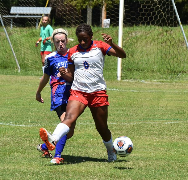 Heritage Academy's Sarah Curtis, left, battles for control of the ball during a high school girls soccer match last season against Marshall Academy at the River Walk Soccer Complex in Columbus. The Patriots are still on pace for an on-time start for the season opener on Aug. 3.