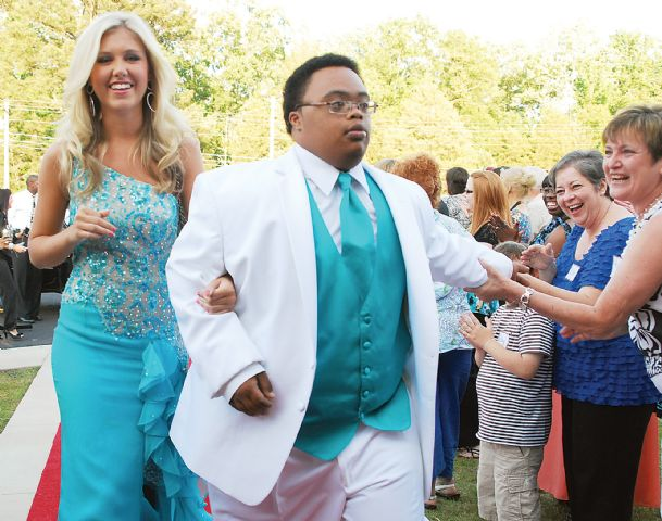 Peter Jones walks with his Joy Prom date, New Hope High School senior Kathryn Mathis, at Mt. Vernon Baptist Church Saturday evening. Jones' teacher, Kay Broome, far right, welcomes him to the dance.