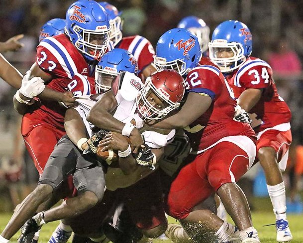 Noxubee County defenders including (from left) Trillo Brown (33), Travorus Hatcher (94), unidentified (52), and Chaunssey Triplett (34) team tackle Louisville quarterback Bryandrea Shumaker (9) during the fourth quarter of their football game Friday night Aug. 23, 2019 in Macon, Miss.