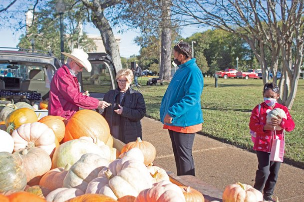 Mark and Marilda O'Bryant, left, sell a pumpkin to Kalin Tolliver, far right, and her mother, Mattie, at the