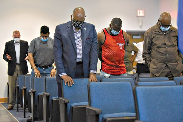 Members of the audience bow their heads in prayer to end the Policing in Columbus town hall meeting on Tuesday at the Columbus Police Department. About 30 people sat in the audience during the town hall.
