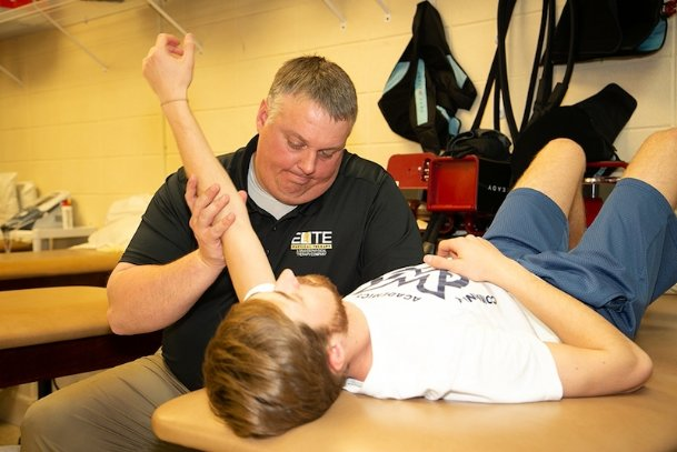MUW head athletic trainer Jason Miller stretches the arm of Owls baseball player Kamryn Randolph to prepare Randolph for practice that day.