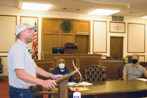 Blake Hill, left, vice president of Phillips Contracting, explains to the Oktibbeha County Board of Supervisors at its Monday meeting that the Columbus-based company waited months for AT&T and 4-County Electric Power Association to move utility wires on Longview Road. Phillips accepted a $2.2 million contract in July 2019 to pave the road, which area residents have waited for years to happen, and Hill said the company had been hoping to start the project in the spring and be almost done by now.