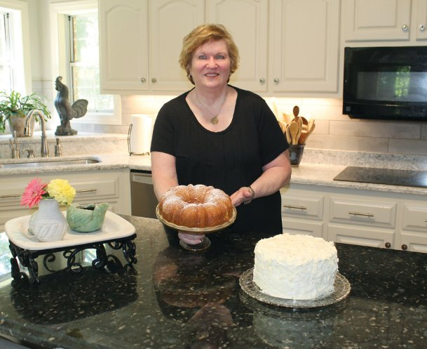Pam Rhea holds an apricot nectar cake Monday at her home in north Columbus. The frosted cake is a mandarin orange cake, with mandarin oranges in the cake and pineapple in the frosting. While working from home since March 17, Rhea has been making some of her mother's signature recipes.