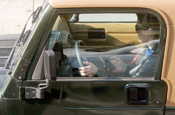 A driver uses a phone while driving in Los Angeles in this Wednesday, Dec. 14, 2011, file photo.
