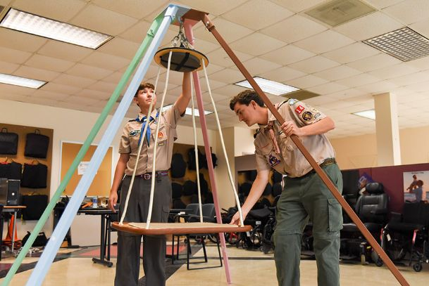 Troop 45 Eagle Scout Simon Banzhaf, 15, of Starkville, and his father, George Banzhaf, assemble a platform swing at the T.K. Martin Center on the Mississippi State University campus Wednesday afternoon. Simon built the stand for the platform swing which can be easily disassembled for storage and relocation. The swing is used for children with sensory overload problems to keep them from being over stimulated or understimulated.