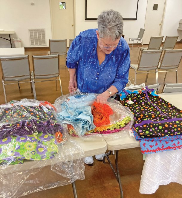Tammy Craddock of Columbus sorts dresses she made that are on their way to El Salvador, to be distributed by a ministry. Craddock was compelled to make the garments after talking to a niece who previously went on a mission trip.