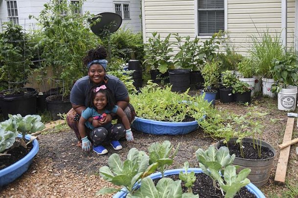 Omini Parks and her daughter, Gibson, 5, pose for a portrait in their garden outside their home in Starkville on Thursday. Parks started the vegetable garden as an educational activity over spring break.