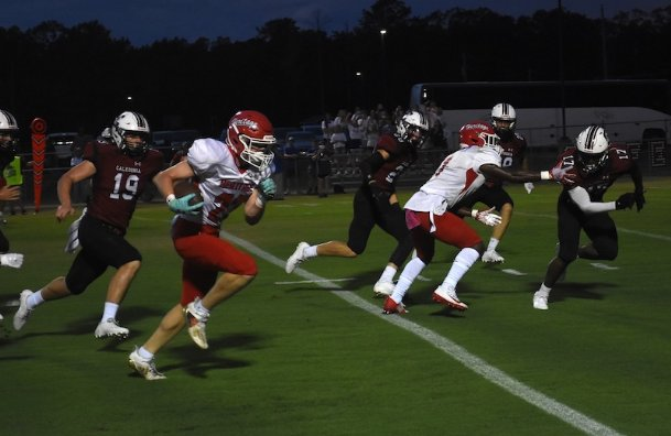 Heritage Academy wide receiver Trey Naugher (23) takes a screen pass for a touchdown Friday night against Caledonia. It was the first of Naugher's three touchdowns in the Patriots' 28-21 win.