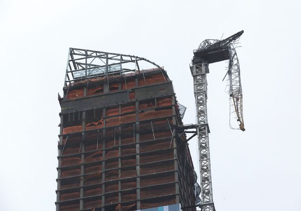 A construction crane atop a luxury high-rise dangles precariously over the streets after collapsing in high winds from Hurricane Sandy, Monday, in New York.