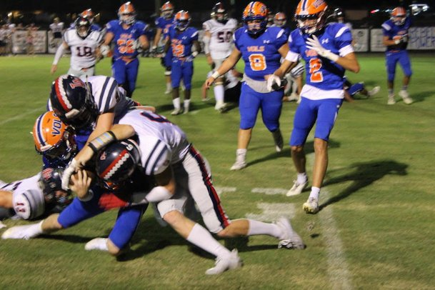 Starkville Academy quarterback Randall Futral is crunched by a gaggle of Leake Academy defenders on Friday in Starkville. The Rebels downed the Volunteers on a go-ahead touchdown run with 35 seconds left in Friday's shootout.