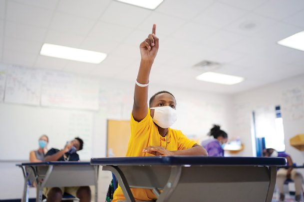 Elijah Butler raises his hand to answer a science question on the first day of school on Thursday at Stokes-Beard Elementary. Columbus Municipal School District started classes with 60 percent of students signed up for hybrid learning - a combination of in-person and virtual - and 40 percent attending classes online only.