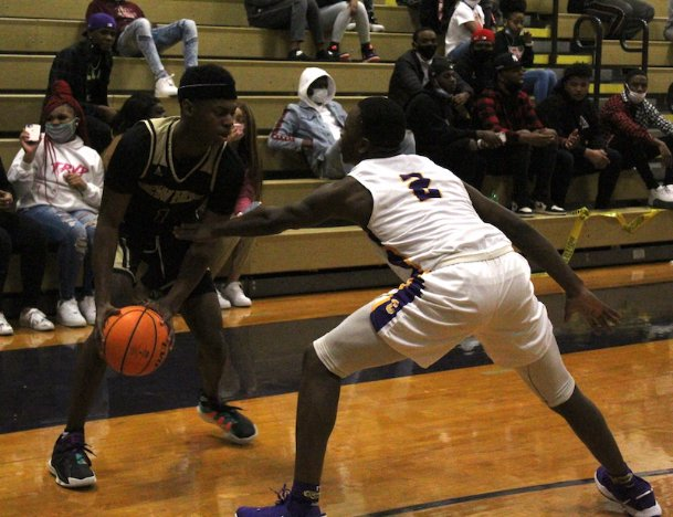 New Hope senior Jorden Edwards (1) is defended by Columbus junior Willie Young (2) during the second quarter of Friday's game in Columbus. The Trojans won 60-39.