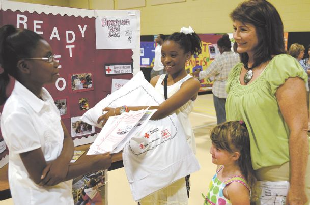 """From left, Sale Elementary School students Chelsey Little and Morgan Williams, both 10, give an """"elevator speech� about the American Red Cross to Cindy Parker and 3-year-old Gabby Getter Monday at the Columbus school. Working in teams, Sale's fifth-graders researched and marketed nonprofit organizations for their International Baccalaureate exit project on advertising. Chelsey is the daughter of Rita and Everett Little. Morgan's parents are Jamika and Derrick Williams."""