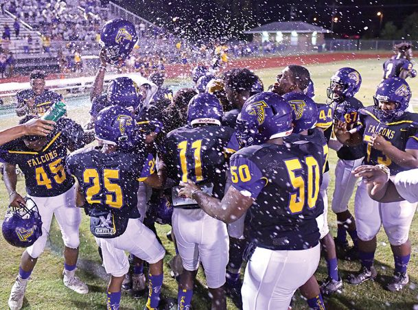 The Columbus High School football team celebrates after winning Friday's homecoming game against Lanier High School. The Falcons defeated the Bulldogs 13-12.
