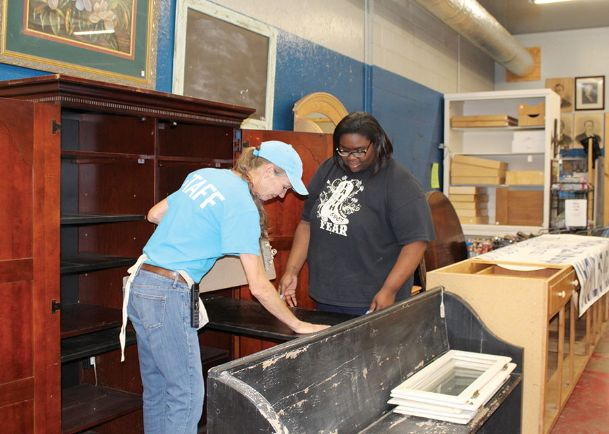 Columbus-Lowndes Habitat for Humanity ReSale Store Manager Abby Davis, left, and Chelcee Ezell position a donated entertainment cabinet at the store on Gardner Boulevard in Columbus Wednesday. Davis became involved with Habitat for Humanity through a house build Heritage Academy participated in 10 years ago. Ezell used to volunteer at the ReSale Store when she was a student a Heritage Academy; she is now on the Habitat staff.