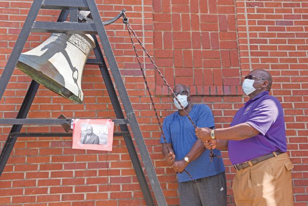 From left, Lowndes County District 5 Supervisor Leroy Brooks and Columbus Mayor Robert Smith ring a bell at 10 a.m. on Thursday outside Missionary Union Baptist Church in Columbus to honor civil rights leader and Congressman John Lewis, who passed away on July 17. Brooks and Smith rang the bell in sync with churches throughout Atlanta and the South on the day of Lewis' funeral. Lewis wrote an essay shortly before his death and asked that it be published on the day of his funeral.