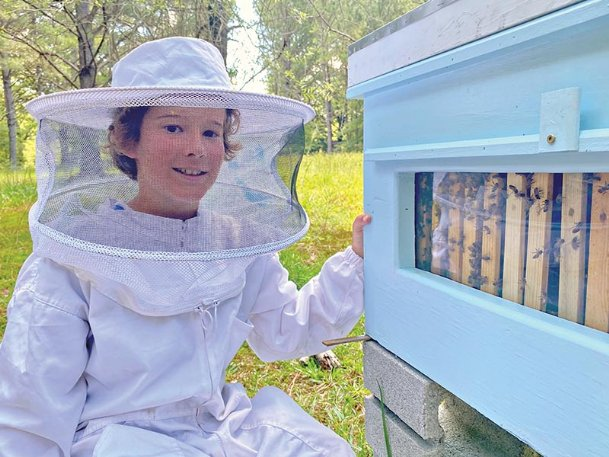 Charlie Sanders, 10, sits next to one of three hives he tends at his home in the Craig Springs community near Sturgis. Charlie, who has been tending bees for about a year makes and sells candles from the wax bees produce.