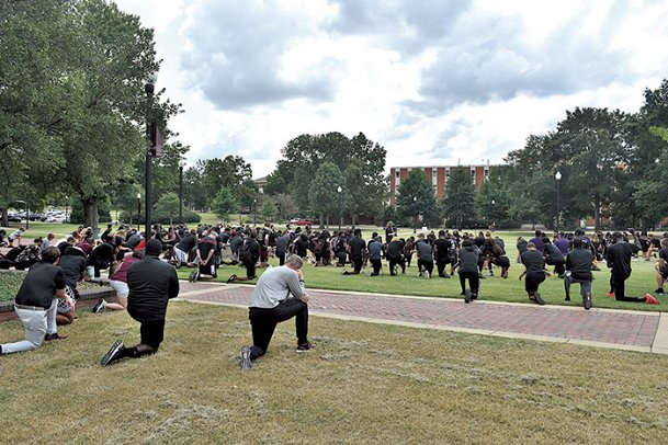 "Protesters kneel Thursday at the junction at Mississippi State in remembrance of George Floyd. ""The protesters, made up primarily of MSU student athletes, knelt for eight minutes and 46 seconds.�"