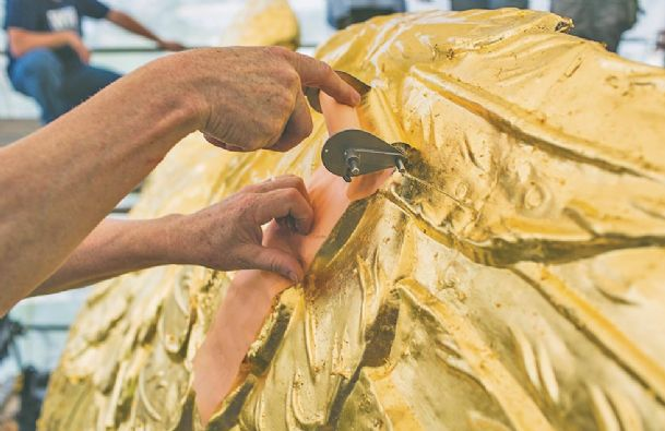In this photo taken April 26, a craftsman applies a fresh layer of gold leaf on the eagle's textured surface in Jackson.