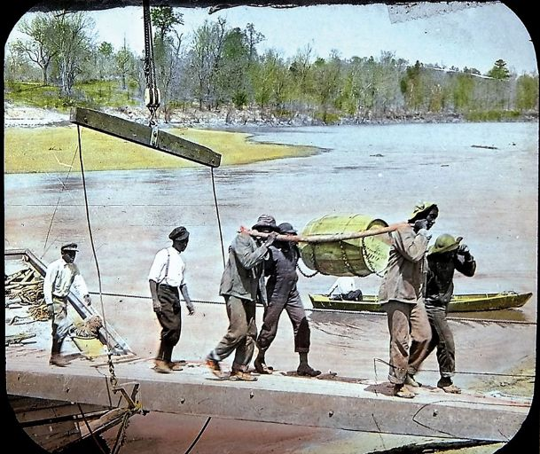 Richard Amerson, a Livingston, Alabama blues singer recalled work chants from his days as a roustabout on an Alabama steamboat loading and unloading goods. In this 1910-1915 photo, roustabouts are unloading barrels of molasses from a Tombigbee River steamboat.
