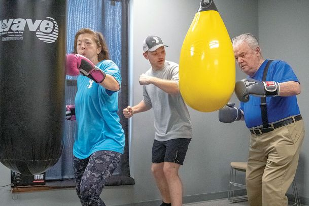 YMCA Adaptive Fitness Coordinator Salem Gibson, center, gives pointers to Rick Corey, right, and Gina Kim, left, at a station in the Rock Steady Boxing class at the Frank P. Phillips Y in Columbus Thursday. The program for individuals with Parkinson's disease incorporates exercises adapted from boxing drills to focus on agility, hand-eye coordination, balance, endurance and overall strength. Corey and Kim live in Columbus.