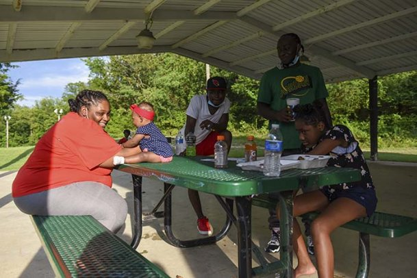 Shaimeka Hemphill, Eriel Monroe, 6 months, Marc Evans, Samuel Hill and Willow Gillespie, 9, sit at a picnic table during the Liberate with Love event on Friday at Moncrief Park in Starkville. The event, organized by the Mississippi chapters of the Black Panthers and the Huey P. Newton Gun Club, encouraged Black citizens to put aside their differences and come together for racial justice.