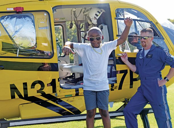 Karemon Hayes, 7, leaps from a helicopter as lead AirCare pilot Pat Glandon looks on during the United Way of Lowndes County's Little Hands, Big Trucks event at the Soccer Complex in Columbus Saturday morning.