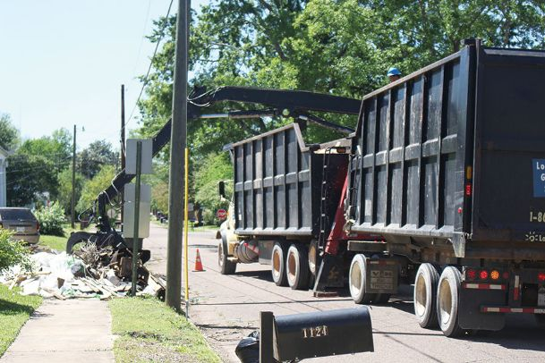 A Looks Great Services crew removes storm debris from a right-of-way on Third Avenue North near 12th Street South. Looks Good has removed more than 1 million pounds of debris since work began last week.