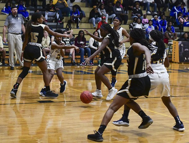 West Lowndes' Averi Sanders attempts to pass the ball to teammate Marvaysha Seals during a game against New Hope on Saturday at West Lowndes High School. West Lowndes defeated New Hope 55-42.