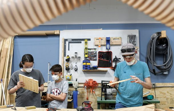 From left, Anna Richey, 15, A.J. Richey, 11, and Sam Moore build phone charging stands during The Idea Shop's Father's Day gift-making workshop on Friday. During the workshop, attendees could make either a charging stand or a set of customized coasters.