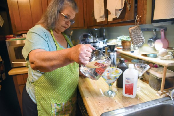 Terry Coffey, pictured Friday at her Columbus home, makes several solutions for use in the house, including an air freshening solution. Hand sanitizer is another DIY product more people are making for themselves while store supplies are low.
