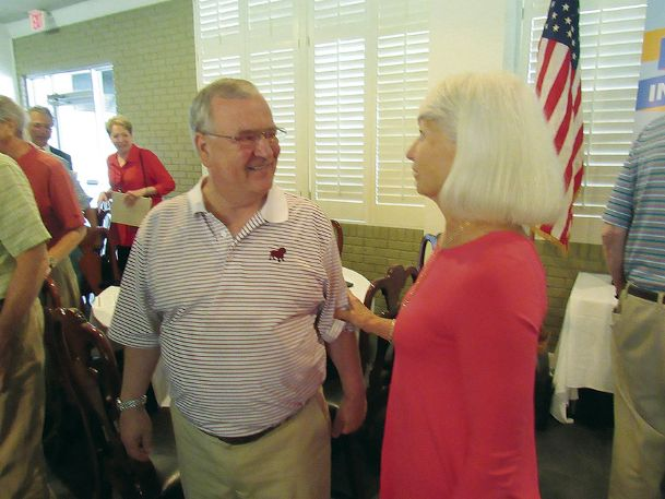 Steve Brandon chats with Starkville Rotary Club member Sandra Harpole Monday after his slide show from his recent trip to Africa. Brandon and his wife, Patsy, have photographed wildlife on all seven continents.