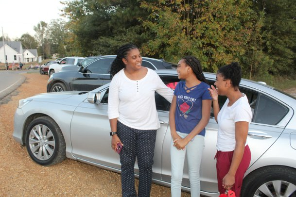 Terra Robinson and her daughters, Luxury Wordlaw, 14, and Tyerria Bryant, 21, wait by their car on Yellowjacket Drive in Starkville for the Starkville High School parade Thursday night. The parade is one of the few major homecoming events that still happened after both the football game and dance were canceled, the latter in response to surging COVID-19 cases in Starkville-Oktibbeha Consolidated School District.