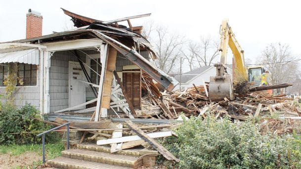 """Bradley Nickoles, operating the backhoe, and Tim Nickoles with Nickoles Construction began tearing down this house located at 804 Main Street on Monday. When asked if this was a one day job, Bradley replied, """"Planning on it.� Dutch Oil obtained a permit to demolish this house but has not revealed its plans for the property."""