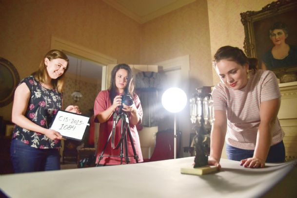 Caryne Eskridge, Lauren Clark Hill and Hannah Boettcher set up an antique item to be photographed at the Amzi Love Home in Columbus. The women, of the Classical Institute of the South, have spent the summer in Southern cities going to antebellum homes cataloging antique objects for an online database.