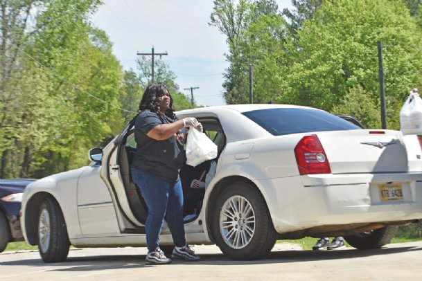Starkville resident SaPerior Patton loads a plate of food into her vehicle Wednesday afternoon. Patton delivered 75 meals across Starkville on Wednesday.