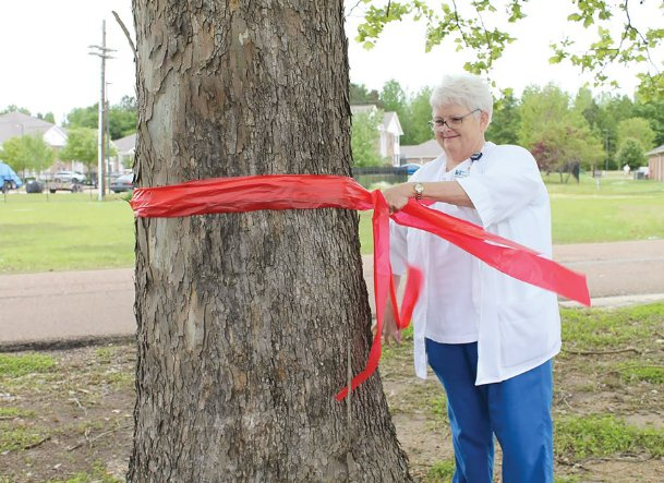 Debra Rhinewalt ties red ribbon around a tree near Baptist Memorial Hospital-Golden Triangle in support of all those working on the health care frontline against COVID-19.