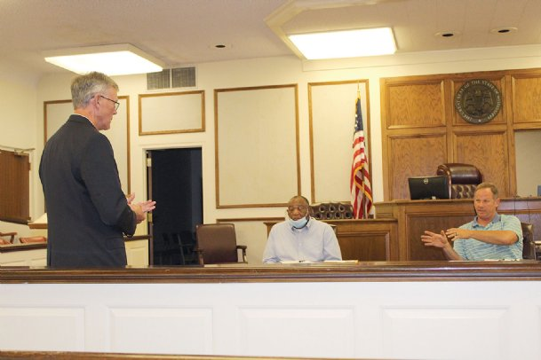 District 1 Supervisor and Board President John Montgomery, right, and Tombigbee River Valley Water Management District executive director David Kennard, left, discuss the county's new membership in the flood control agency at Monday's board of supervisors meeting. The agency completes a few projects in all its member counties every year on a north-to-south rotation, Kennard said.