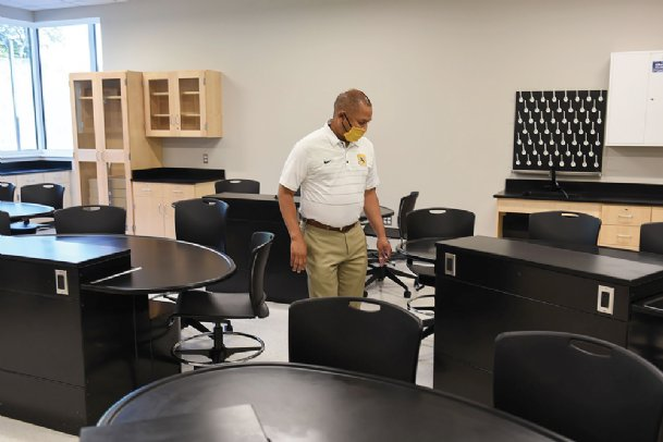 Starkville-Oktibbeha Consolidated School District Superintendent Eddie Peasant walks through a science lab during a tour of The Partnership School on Wednesday in Starkville. Peasant said teachers will be able to adjust the height of the tables depending on the lab activity.