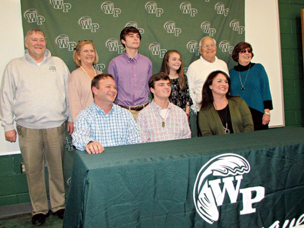 West Point High School senior quarterback Clayton Knight poses for a picture Monday to announce he will play football at East Mississippi Community College in Scooba. His grandparents, Bob Knight and Nancy Knight; his brother, Cade; his sister, Mary Mize; and his grandparents Frank Whitaker and Wanda Whitaker, are standing. His father, Clay, and his mother, Casey, are sitting with him.